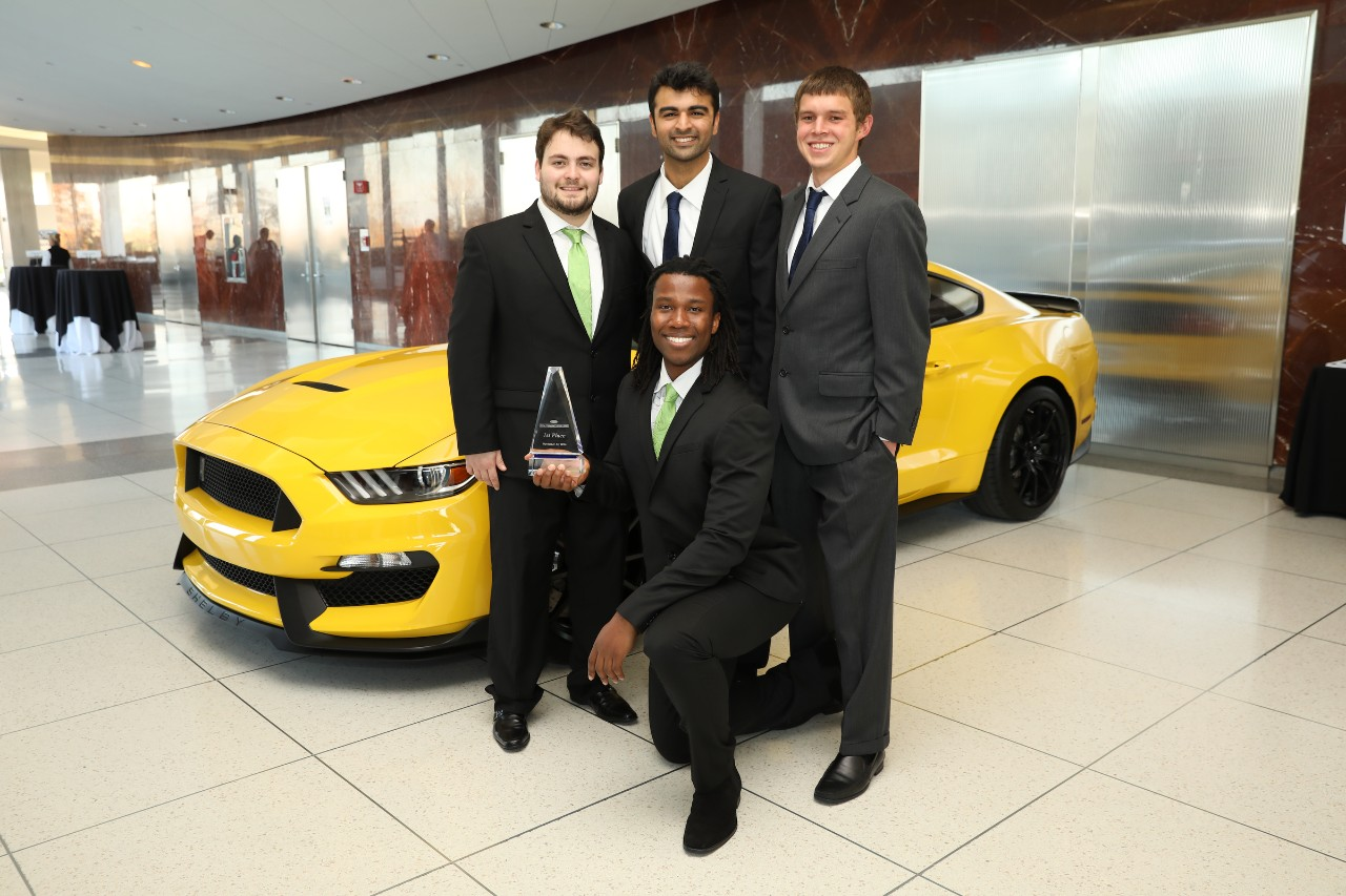 Challenge winners pose next to a Ford vehicle